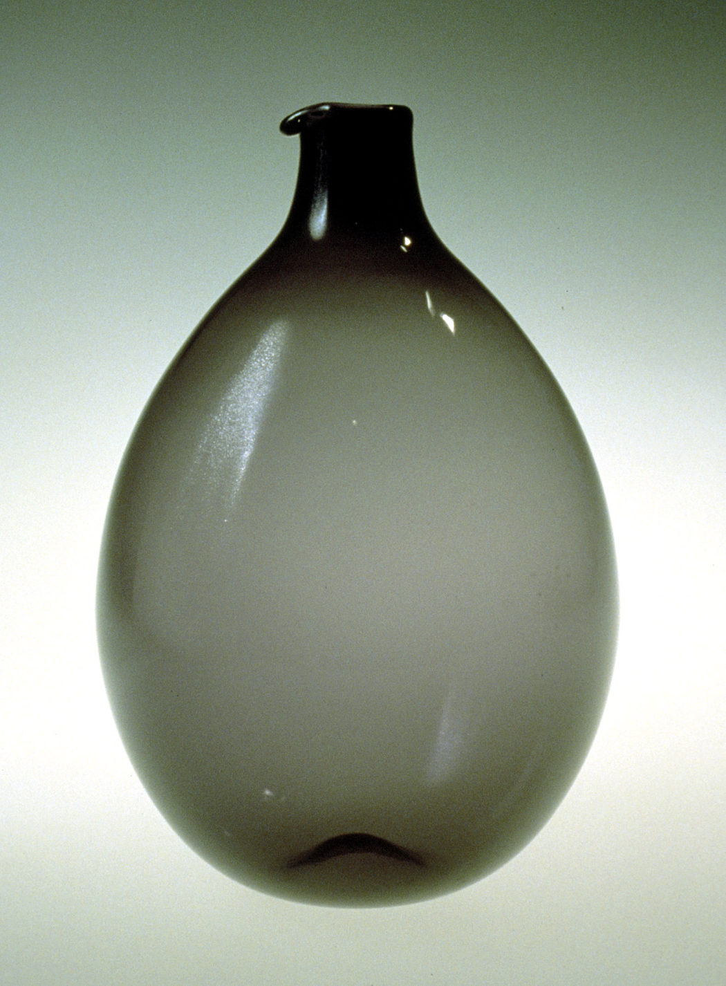 Bulb-shaped decanter in transparent grey glass.