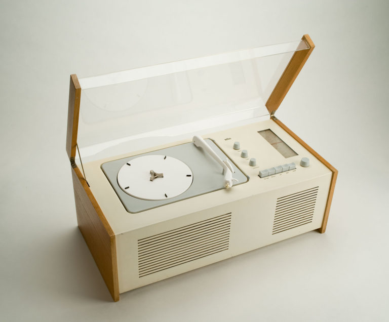 White rectangular plastic record player with wooden side panels. It has a clear plastic lid, a white and grey turntable, and grey knobs and buttons.