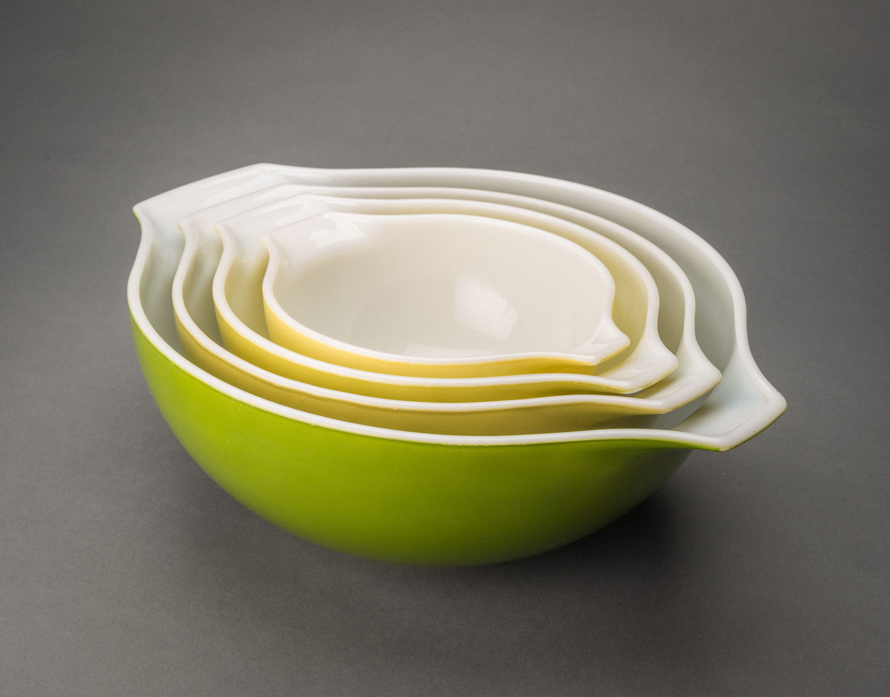 Set of four glass mixing bowls nested together. Each bowl has a white interior. The exterior colors, from smallest bowl to largest, are yellow, yellow-green, pale green, and medium green.