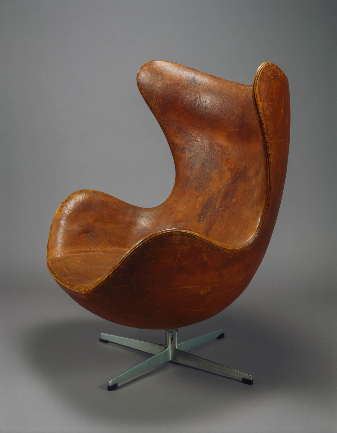 Armchair covered in brown leather as one shell with an X-shaped metal base.