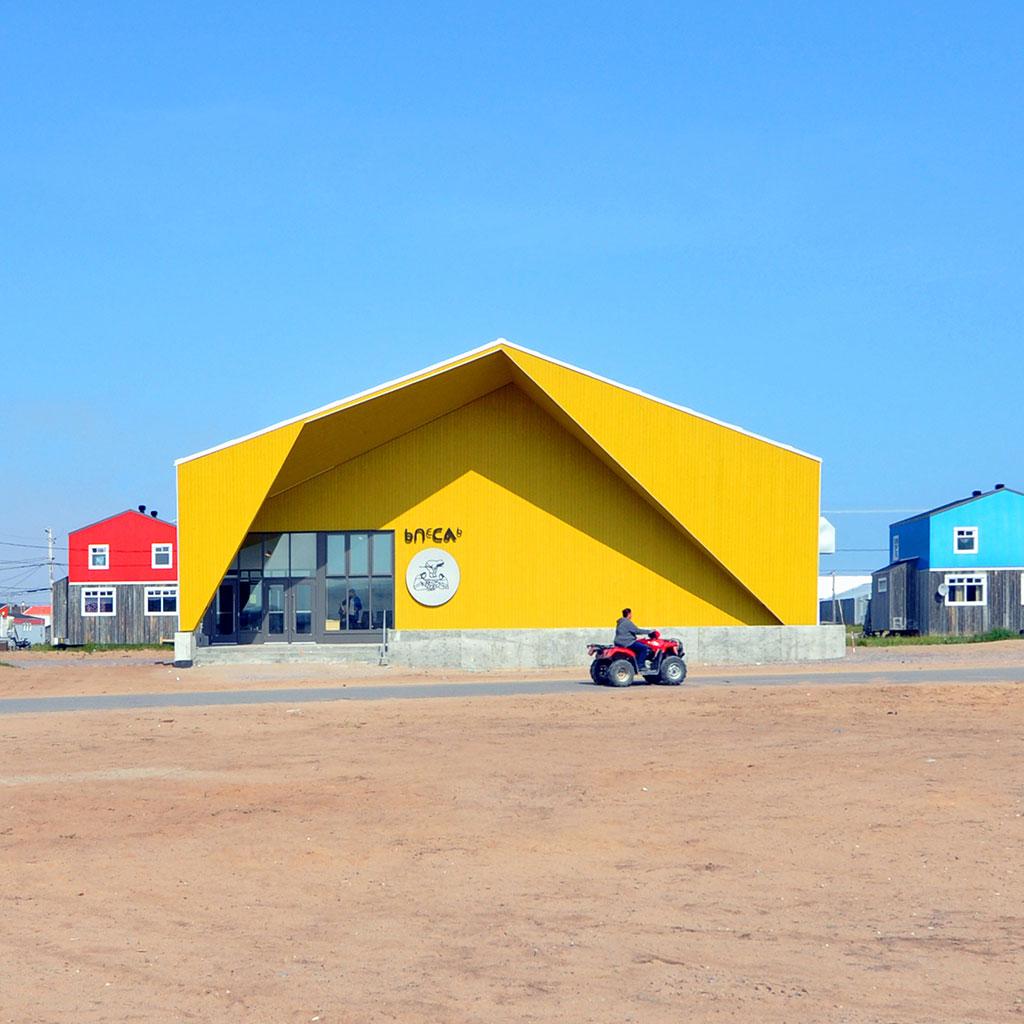 Bâtiment jaune vif, toiture en pente et murs de façade en angle couronnant l'entrée en verre et en acier.