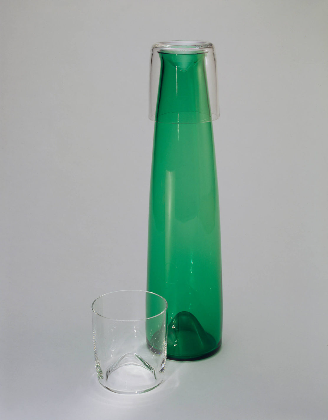 Tall, tapering carafe in transparent green glass with two clear glasses, one placed as a lid on the carafe.