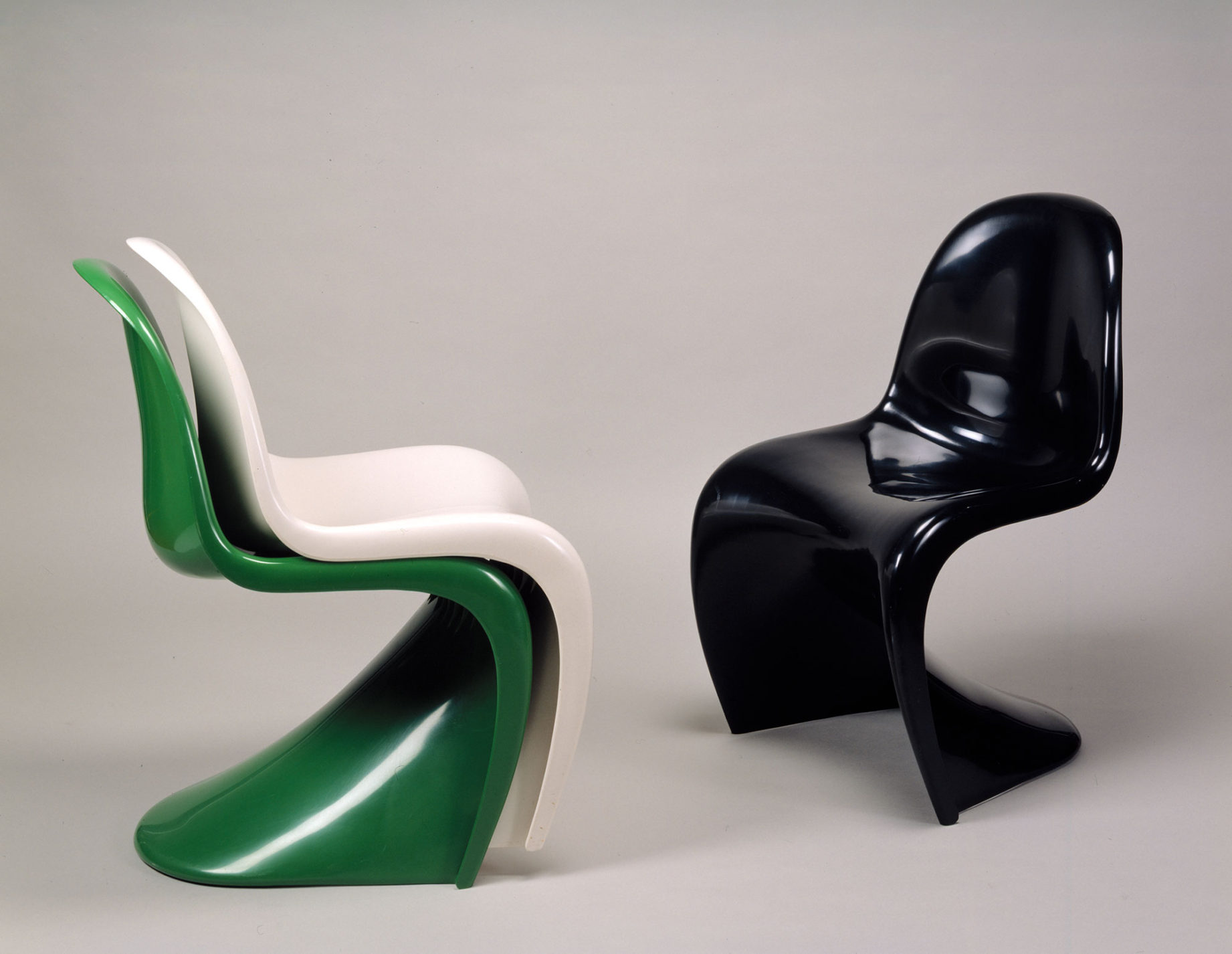 Three curvy plastic stacking chairs in different colors: black, white, and green.