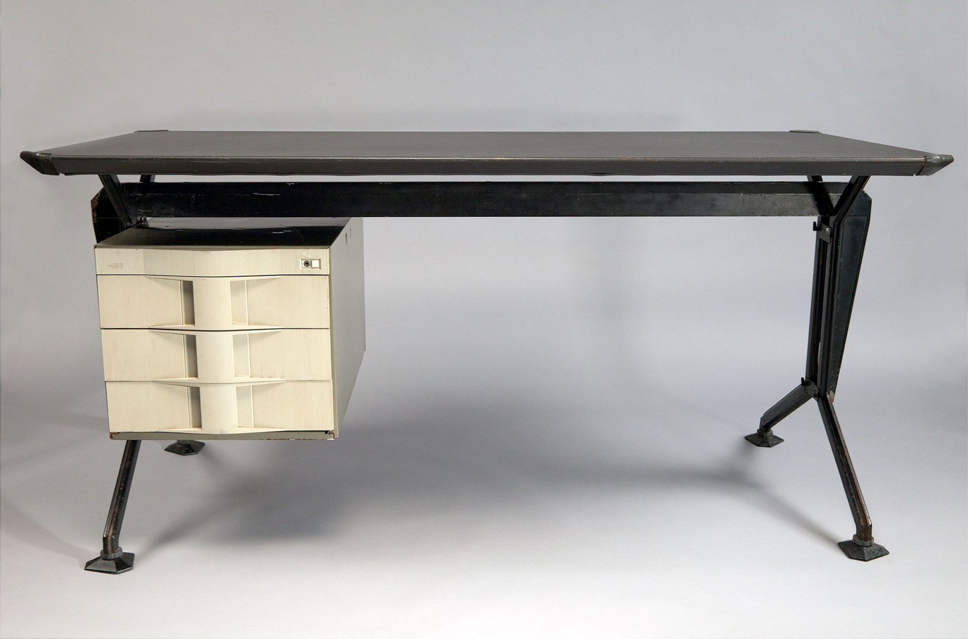 Desk with rectangular plywood top supported by an angular steel frame with a white drawer unit suspended on the left side.