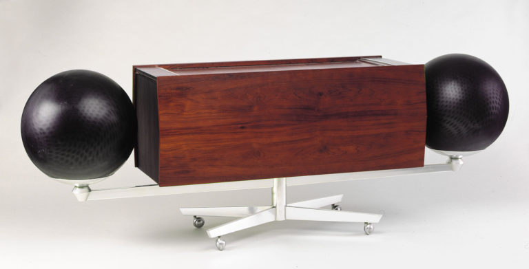 Rectangular wooden cabinet with a large black spherical speaker at each end, mounted on an angular aluminum base.