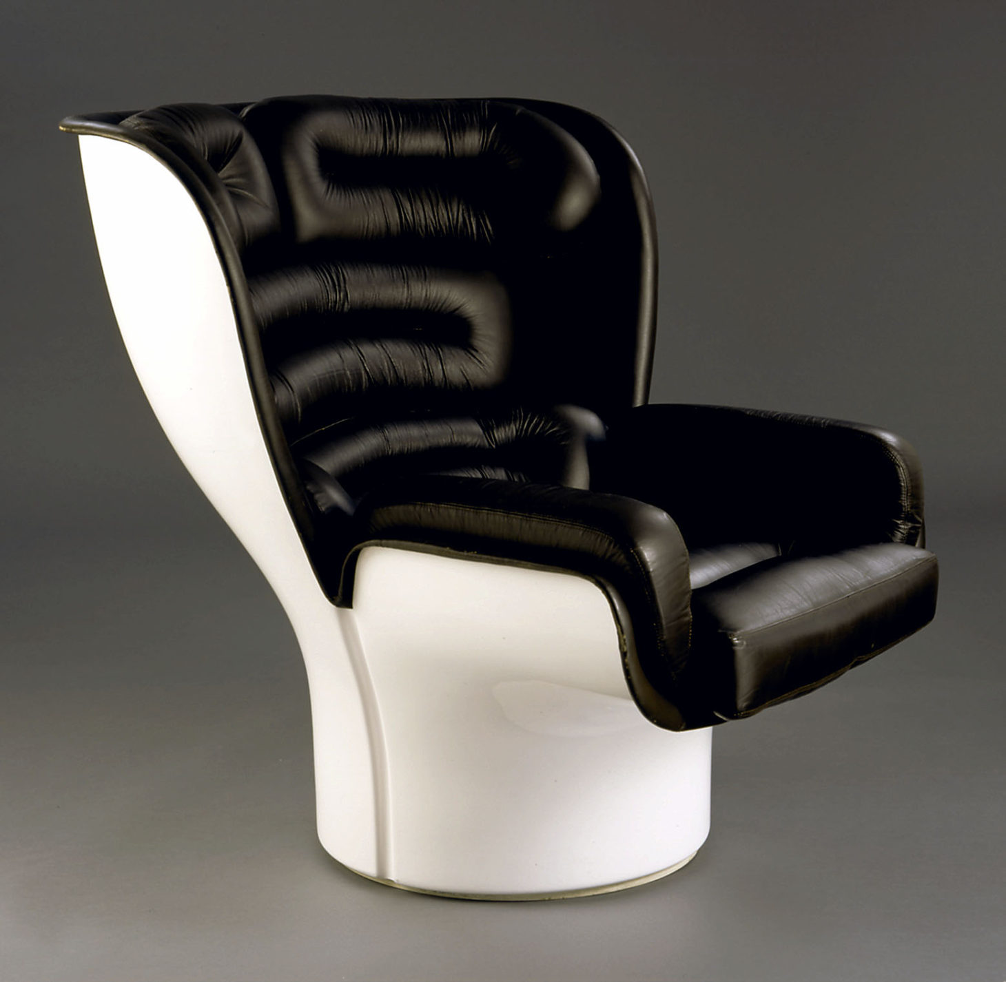 Large armchair with solid white fiberglass frame and thick cushioning covered in black leather.