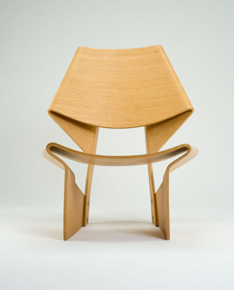 Bent-wood chair. Continuous plywood forms a shaped back, folded backward and joined to rear supports. A second continuous plywood forms gentle concave seat and turns inwardly to form side supports.