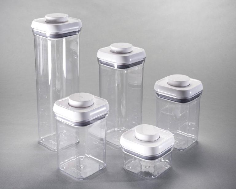 Ensemble de contenants rectangulaires empilables fait de plastique transparent avec couvercles blancs.