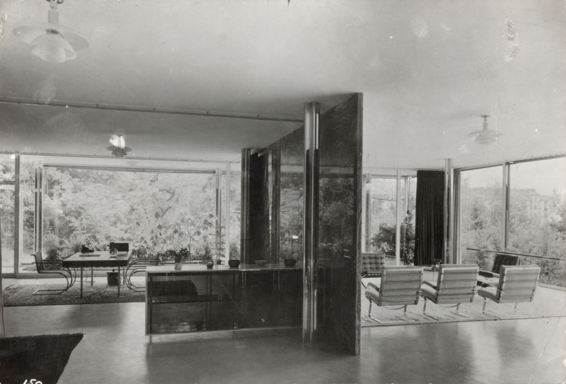 Black-and-white interior view of living and dining rooms showing a minimalistic arrangement of modern furniture including Tugendhat chair.