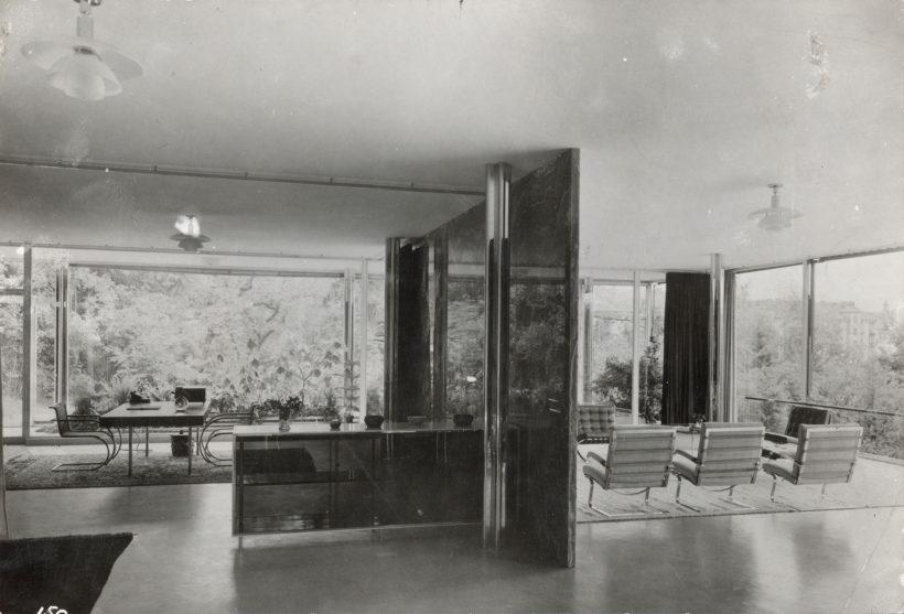Photo en noir et blanc d'un salon et d'une salle à manger au mobilier moderne agencé de façon minimaliste, dont des chaises Tugendhat.