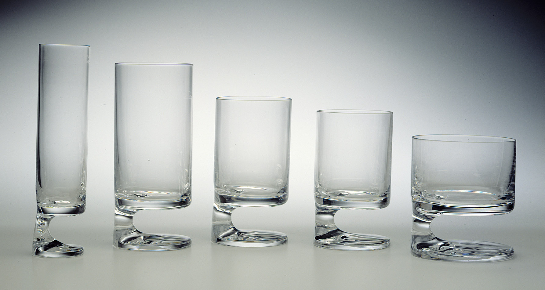 Five glasses in gradating sizes, each a cylindrical form with stem set on one side above a circular base.