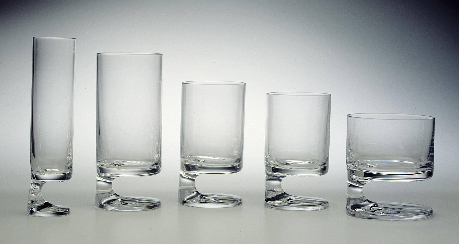 Cinq verres cylindriques de différentes tailles au pied qui s'élève d'un seul côté de la base circulaire.