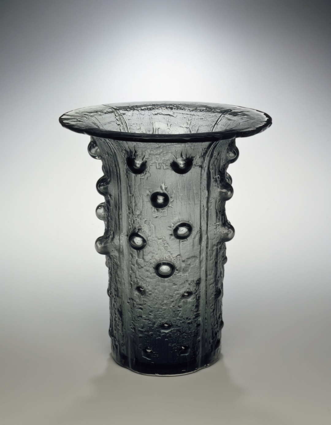 Cylindrical vase of textured glass with bumps and wide flared opening at the top.