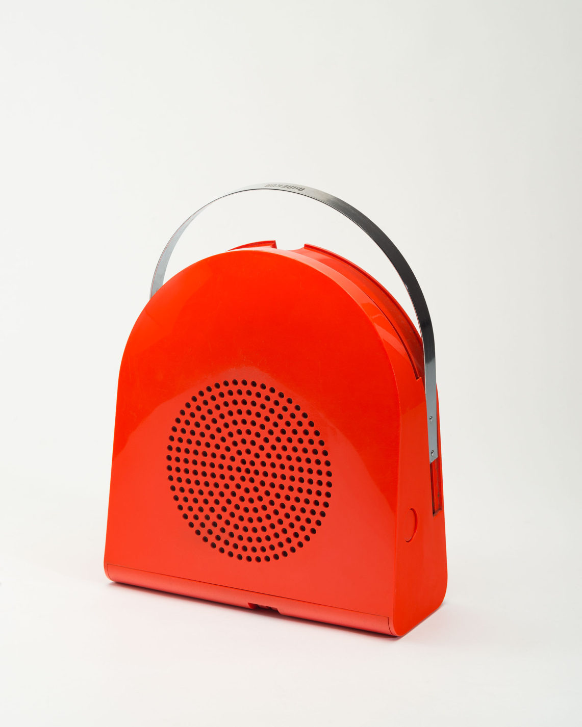 Arched portable record player in red plastic with retractable conforming steel handle at the top. Circular perforated section in the center for speaker.