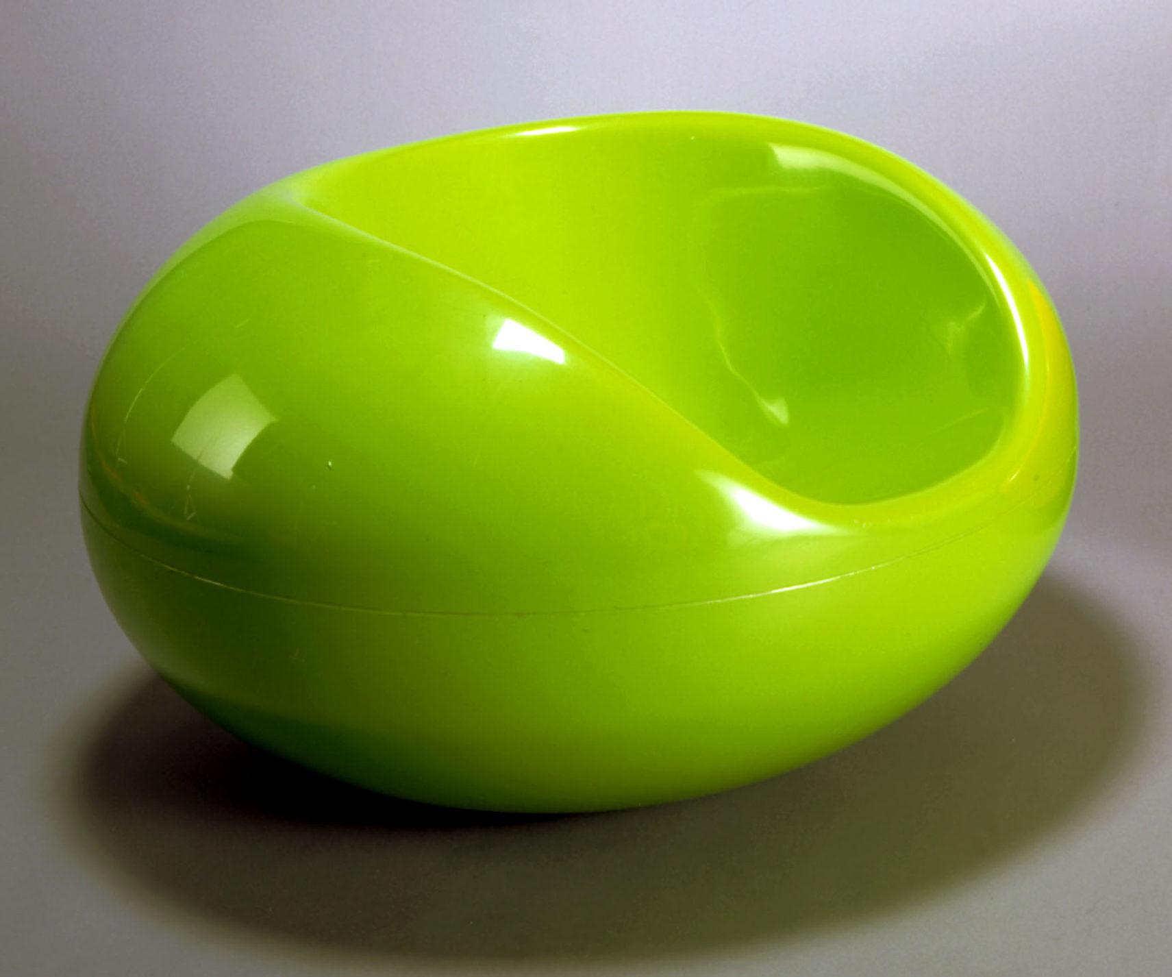 Chaise ovoïde de plastique vert à large renfoncement servant d'assise et de dossier.