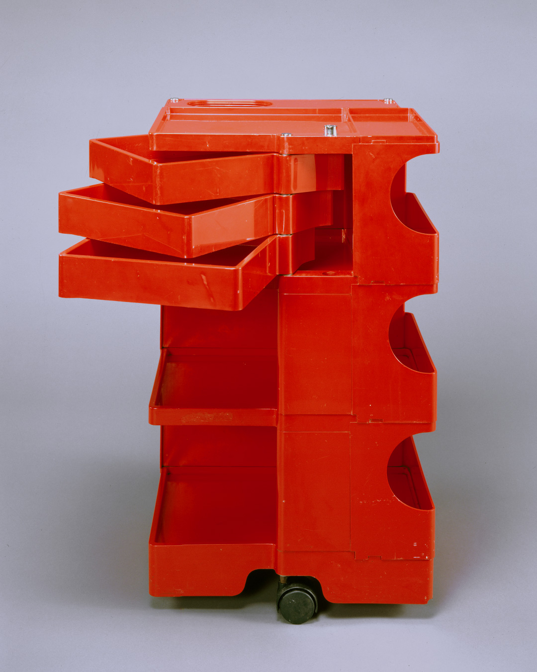 Red plastic storage cart on black wheels with multiple shelves, compartments, and swiveling drawers.