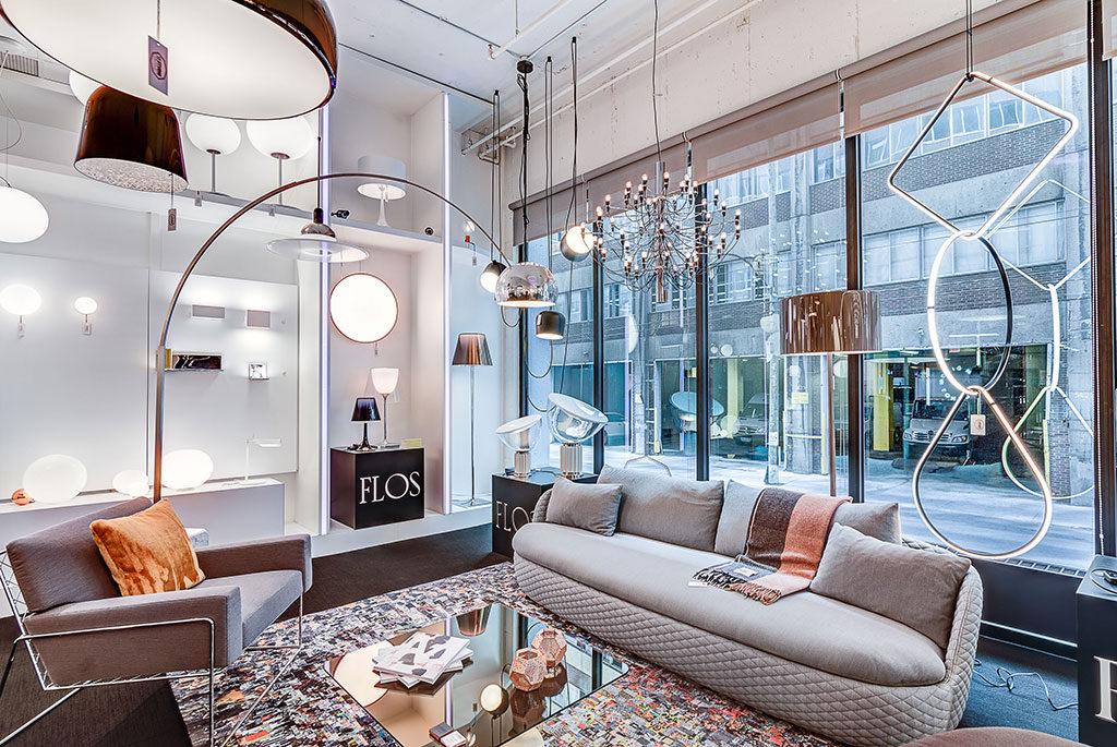 Vue intérieure de la boutique avec son mur de fenêtres; différents meubles et luminaires exposés pour la vente.