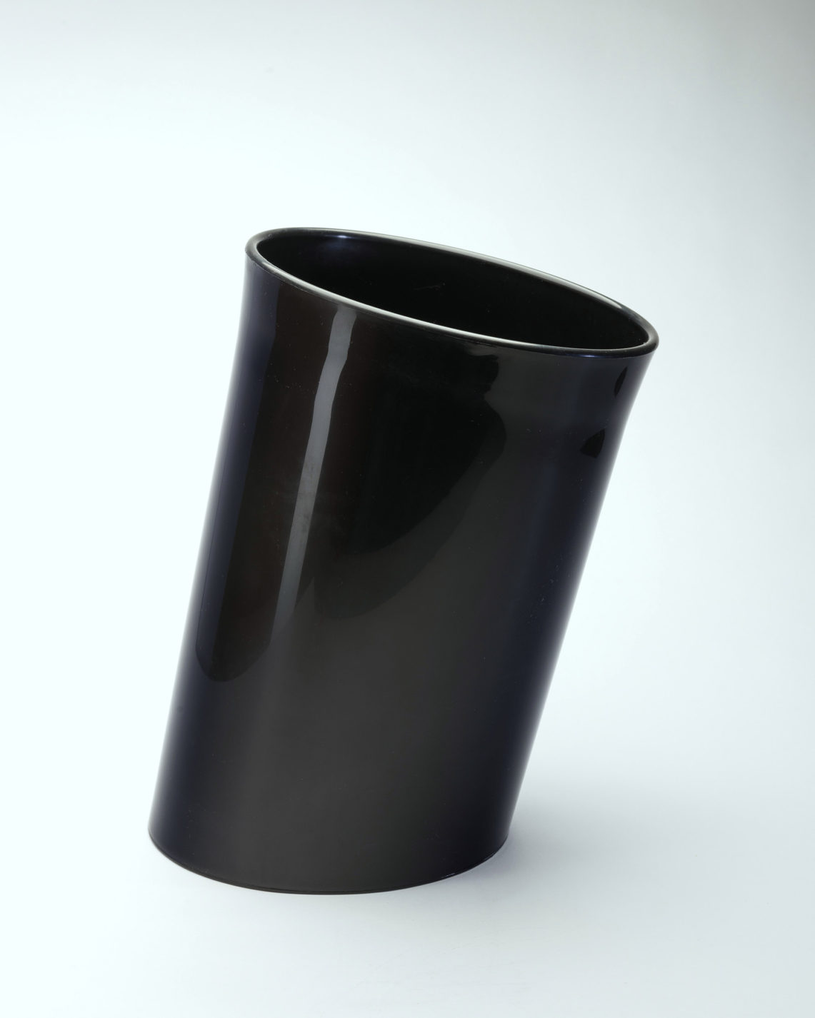 Slanted cylindrical waste basket in black plastic.