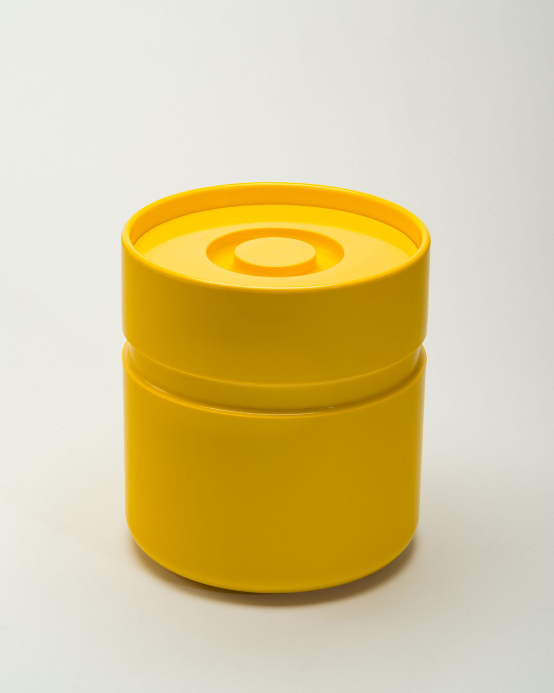 Cylindrical yellow ice bucket with an indented ring around it and a recessed circular handle in the lid.