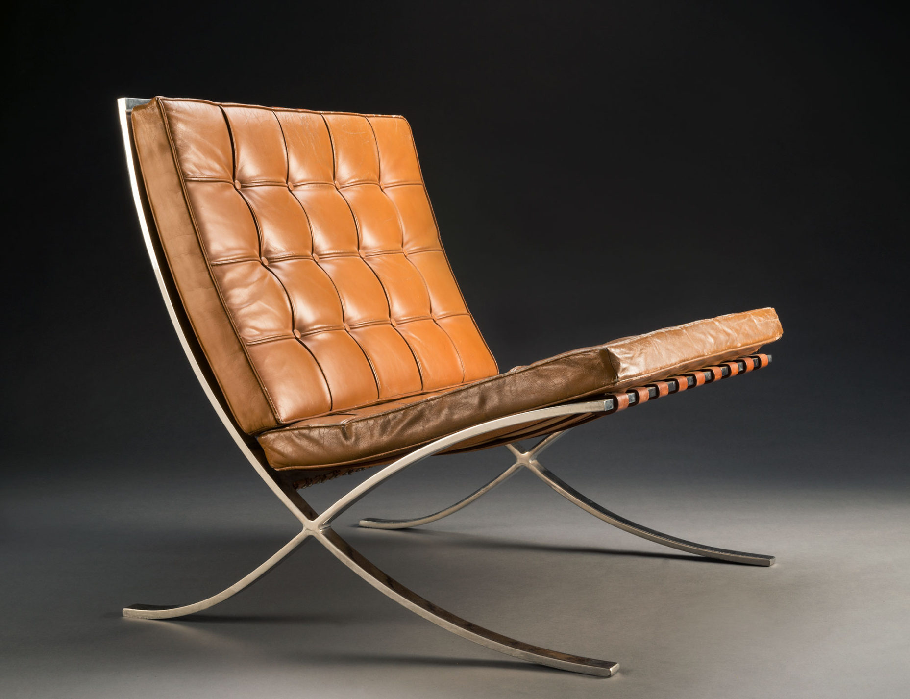 Strap-steel-framed chair with crisscrossing legs and tan leather-covered cushions.