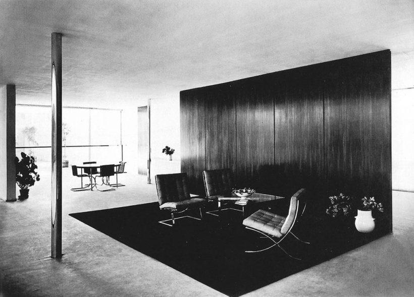 Photo en noir et blanc d'une exposition; mobilier moderne agencé de façon minimaliste avec chaise Barcelona au premier plan.