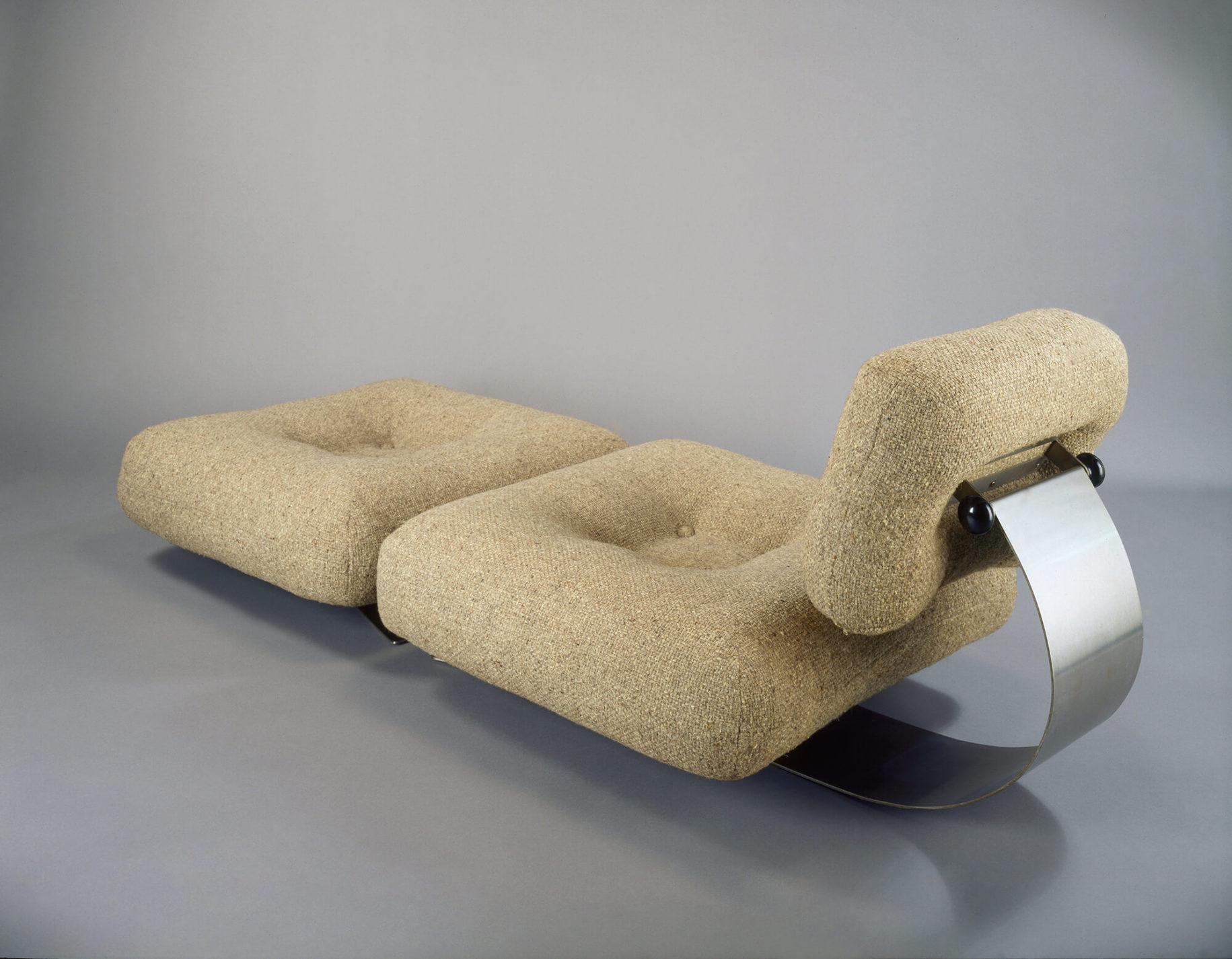 Chauffeuse beige et repose-pieds faits de grands coussins carrés aux coins arrondis creusés au centre. Soutenu par une barre d'aluminium courbée, un coussin rectangulaire sert de dossier.
