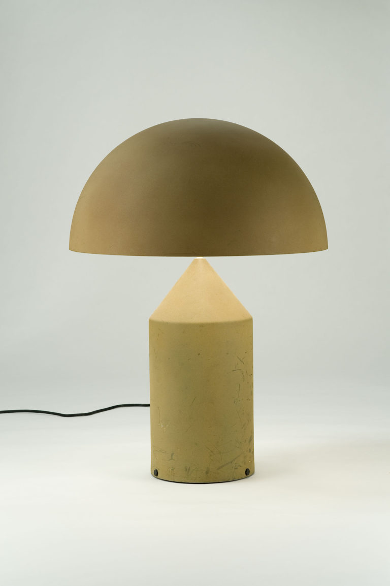 Tan table lamp with a cylindrical base that tapers to a cone at the top, surmounted by a semispherical opaque shade.
