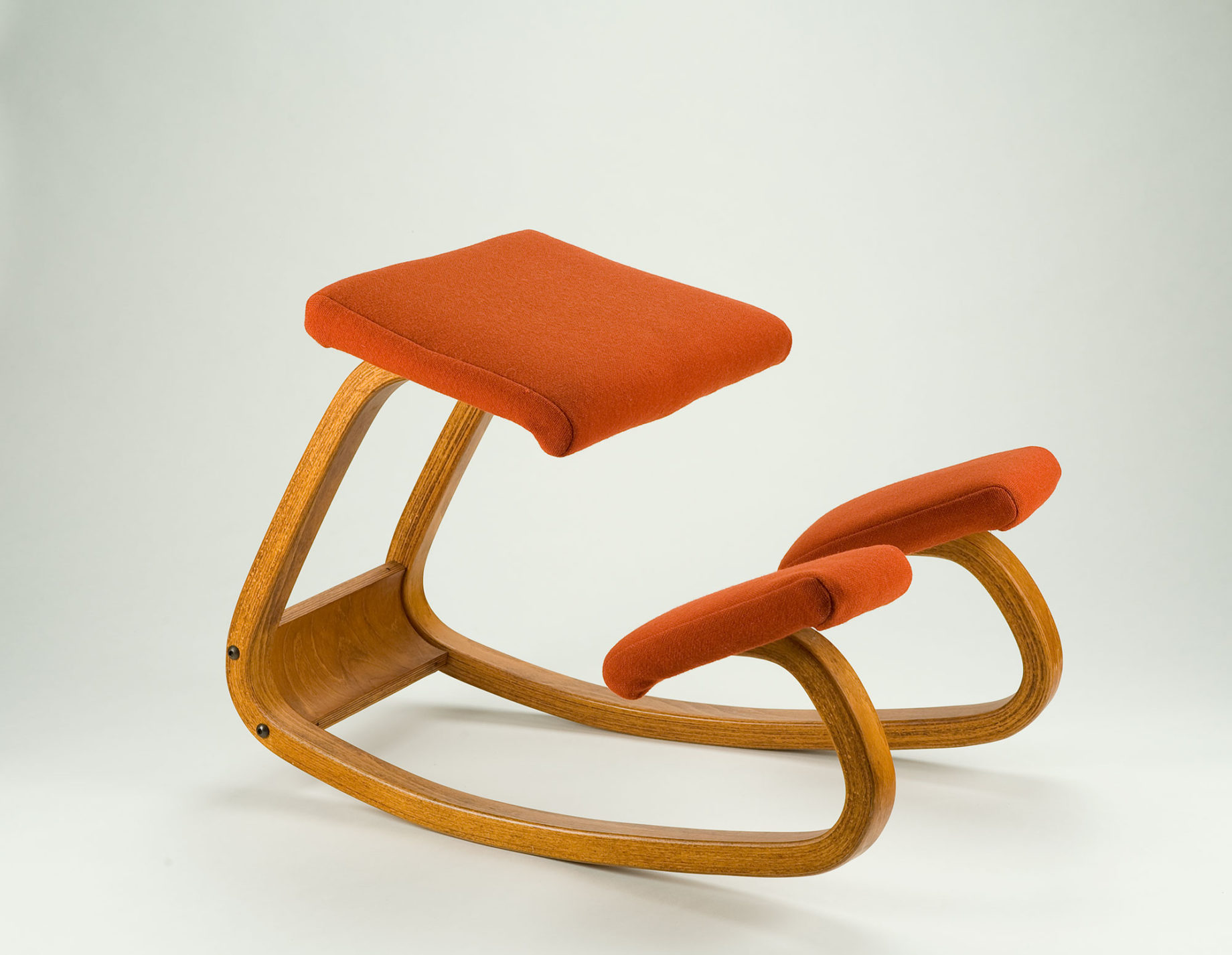Kneeling chair with a continuous bent wood frame and cushioned seat and knee rests upholstered in orange fabric.