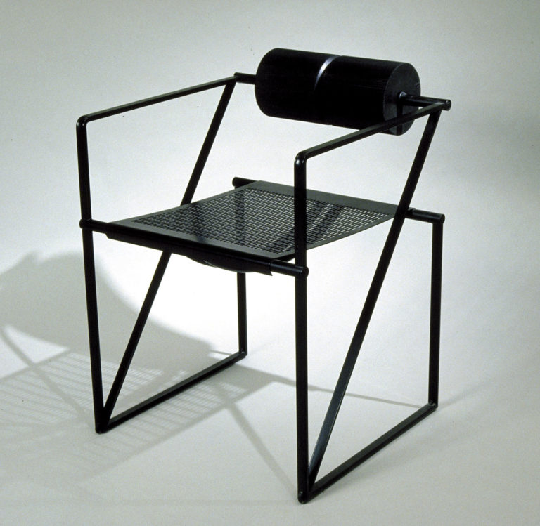 Black armchair with angular tubular-steel frame, perforated metal seat, and horizontal cylindrical cushion for the back.