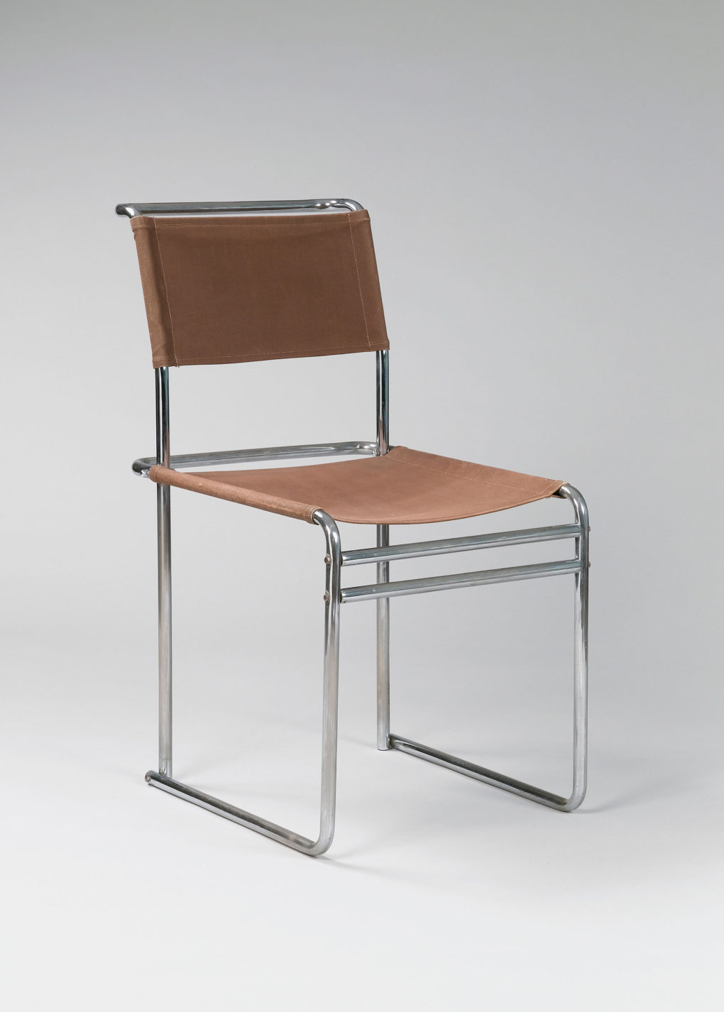 Cantilevered chair with tubular steel frame and a sheet of brown leather suspended between the bars for the seat and another for the back.