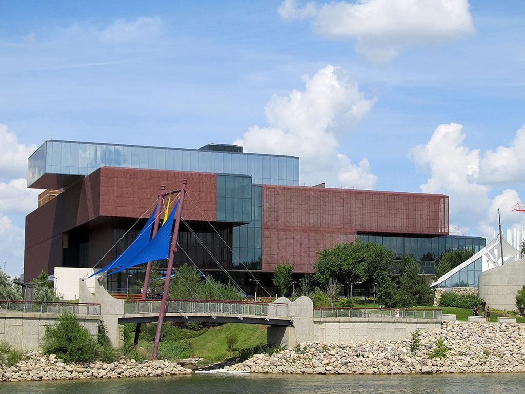 Bâtiment composé de deux larges structures rectangulaires en métal perforé couleur rouille, en béton et en verre.