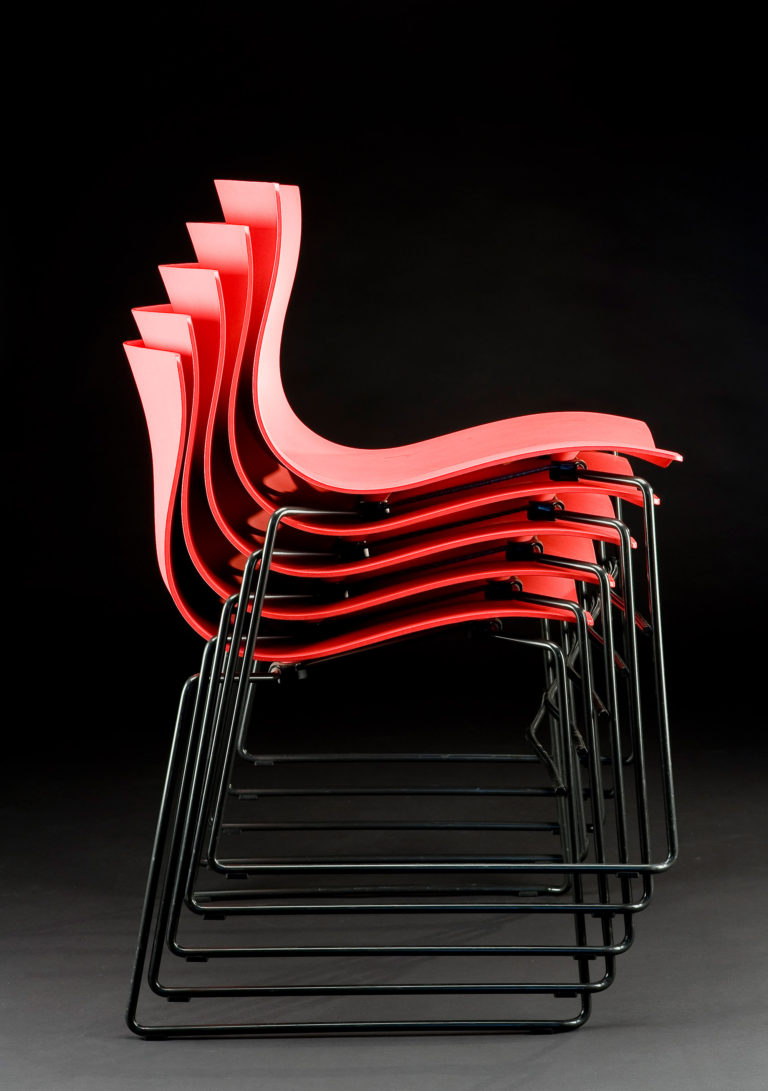 Stack of five chairs, each with undulating shell seat and back in red plastic supported black tubular-steel legs.