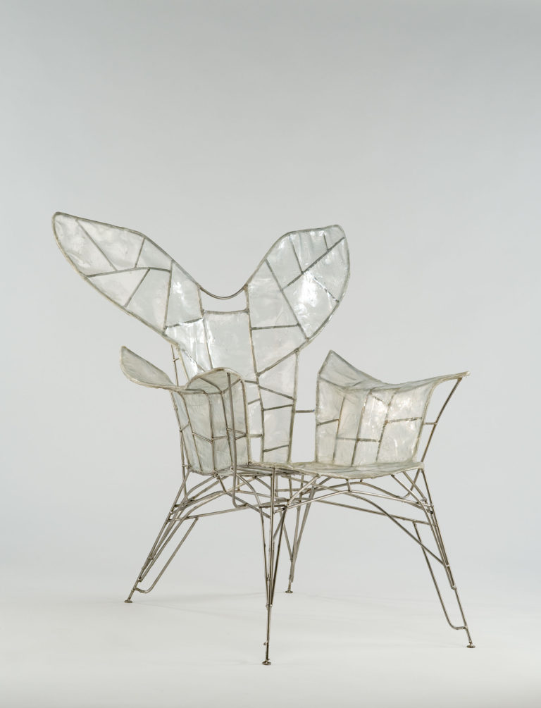 Wire-framed armchair covered in transparent plastic and resembling insect wings.