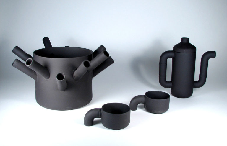 Vase, coffee pot and cups in charcoal grey with elements made to look like pieces of plumbing pipe.