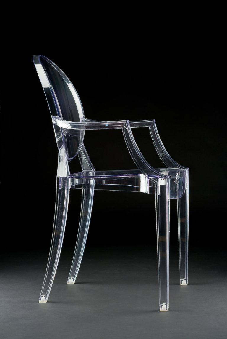 Fauteuil de plastique transparent à dos ovale de la forme des chaises antiques.
