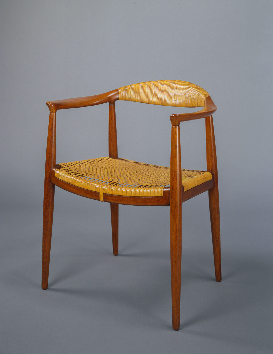 Wooden armchair with slender legs, a wrapped cane back, and a woven cane seat.