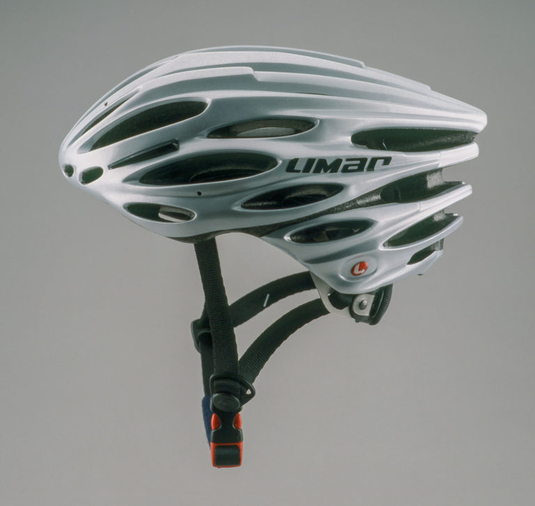 Silver-colored bicycle helmet in a sweeping teardrop shape with numerous ventilation openings and and black brim.
