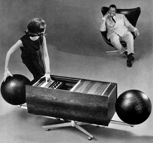 Black-and-white photo of Project G stereo cabinet with large, black, spherical speakers at each end. A woman is touching the control panel of the stereo and turning toward a man seated in a modern leather armchair in the background.