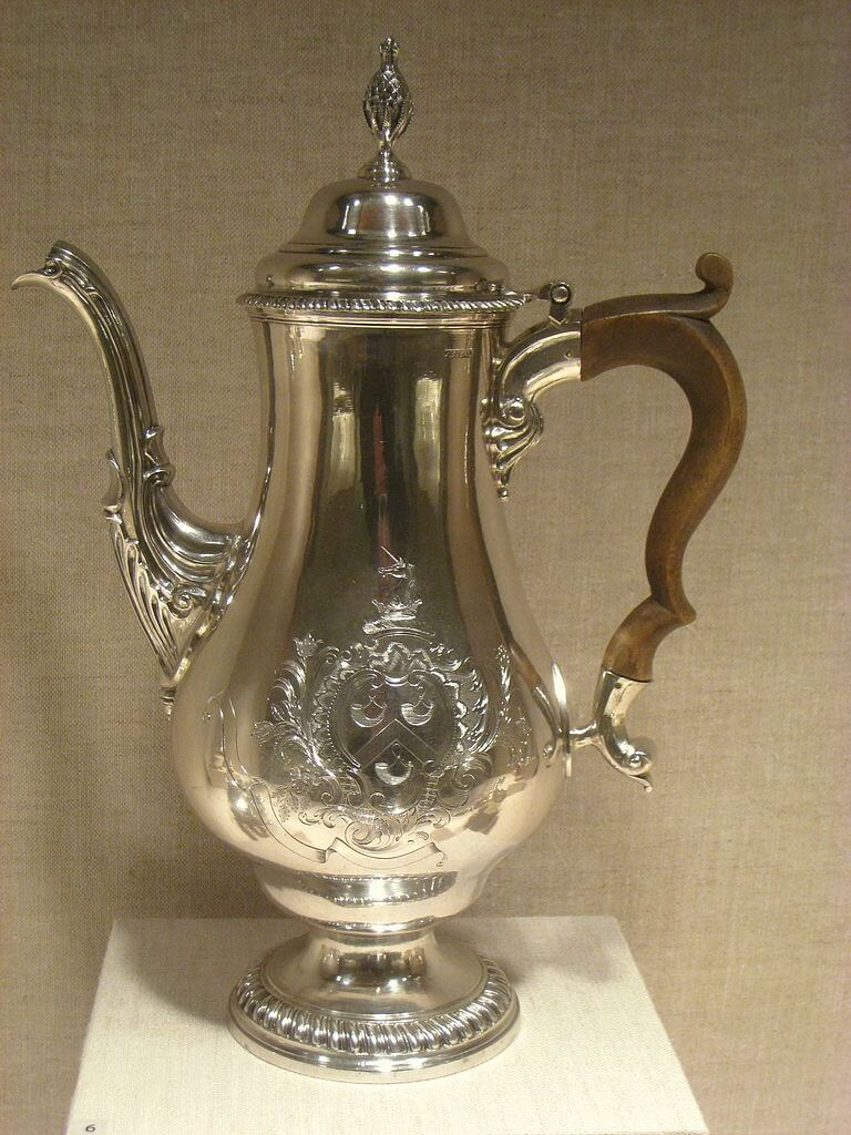 Ornate silver coffeepot with decorative finial and carved wooden handle.