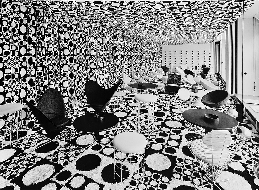 Black and white interior view showing dramatic squares-and-circles pattern on floor, walls, and ceiling, with arrangements of numerous Panton chairs and table.