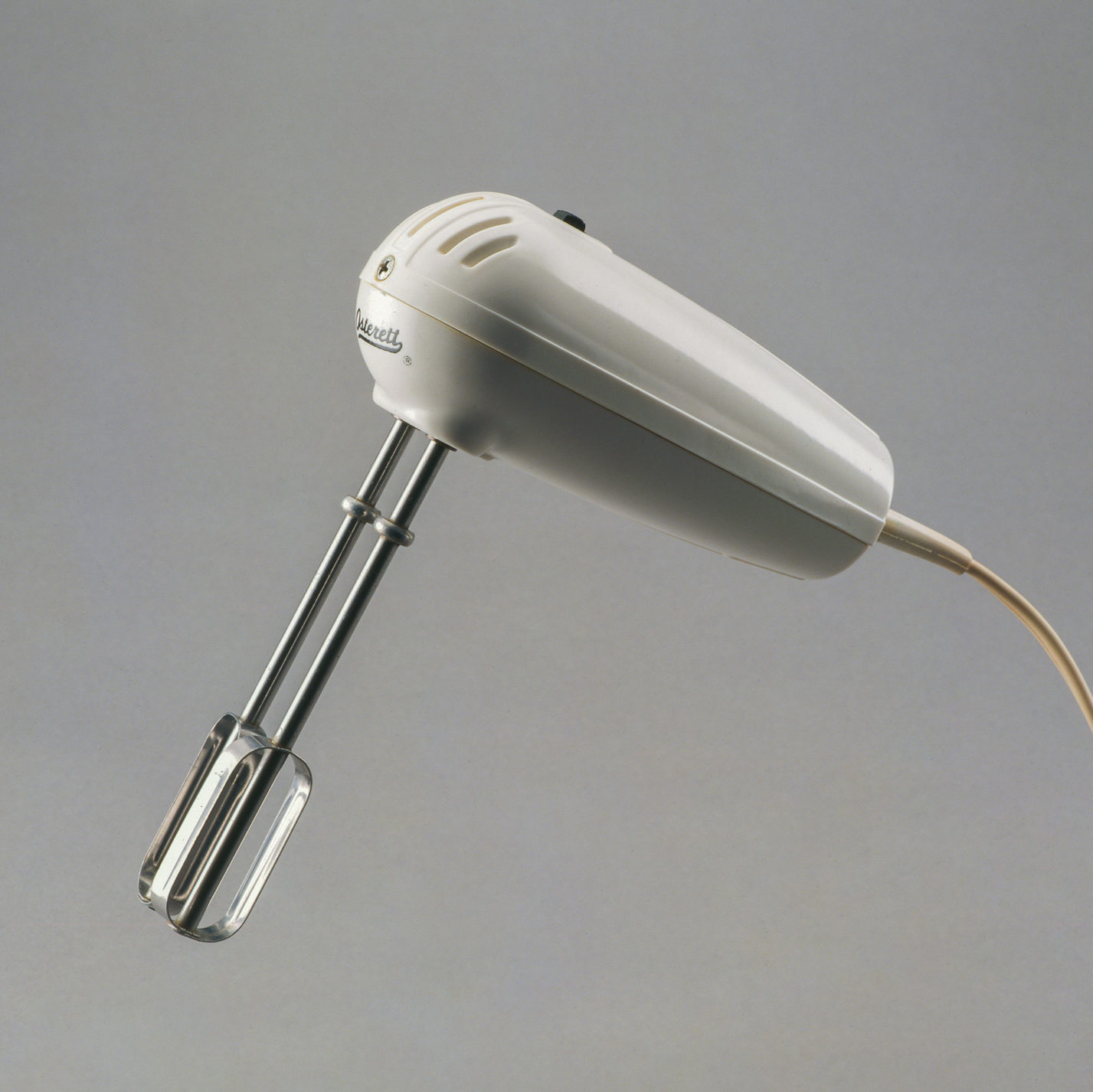 Hand mixer with peg-shaped white plastic body and two metal beaters.