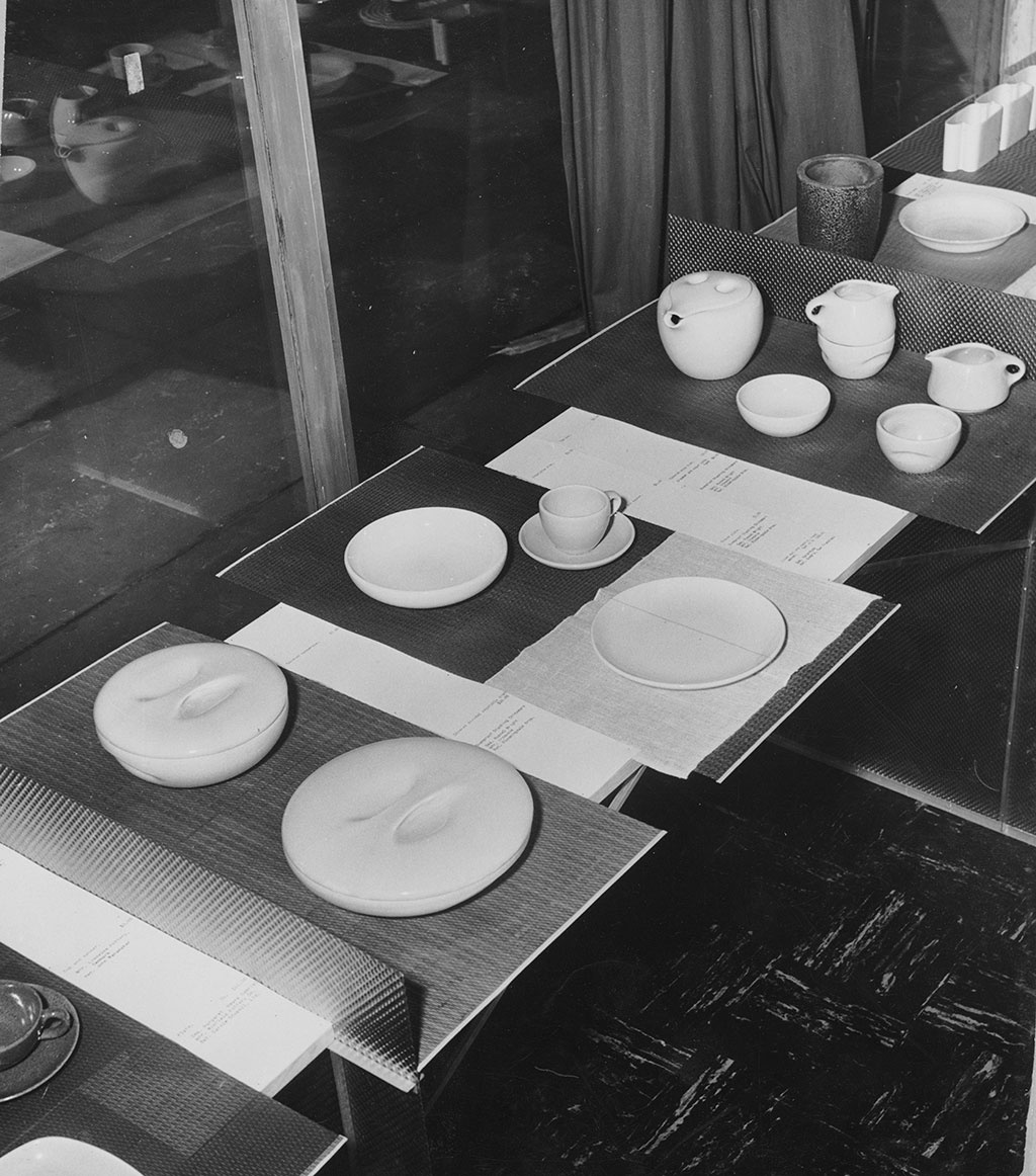 Black-and-white exhibition installation view showing various forms of white ceramic dishes displayed on a long table.
