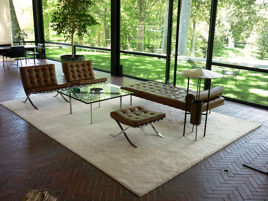 Interior view of glass-walled house showing and arrangement of Mies van der Rohe furniture grouped with Johnson and Kelly's floor lamp.