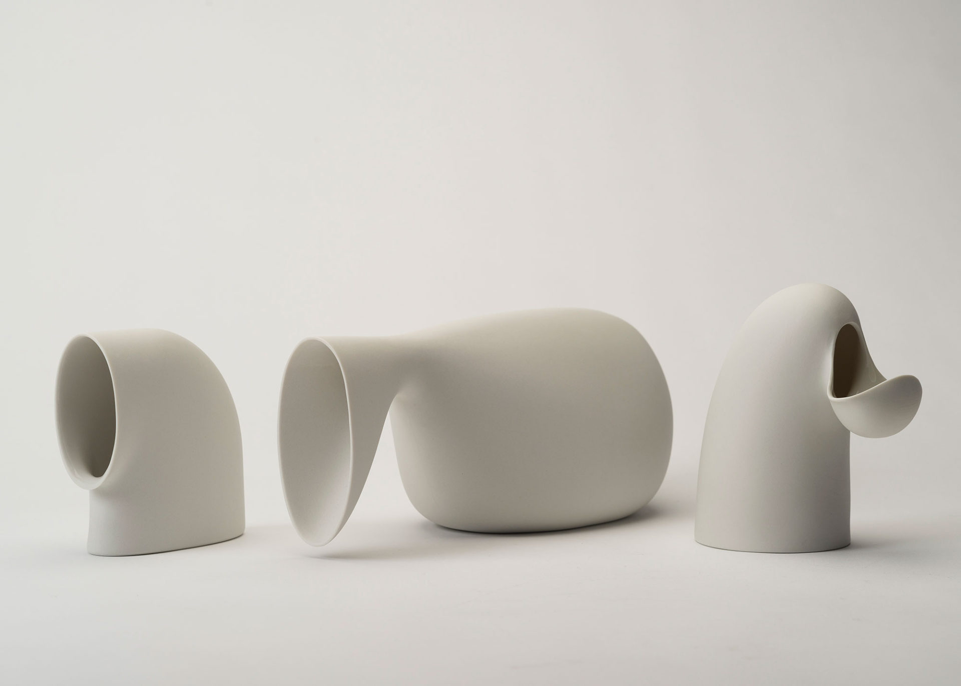 Three vessels in surprising, curving shapes, made of matte white porcelain.