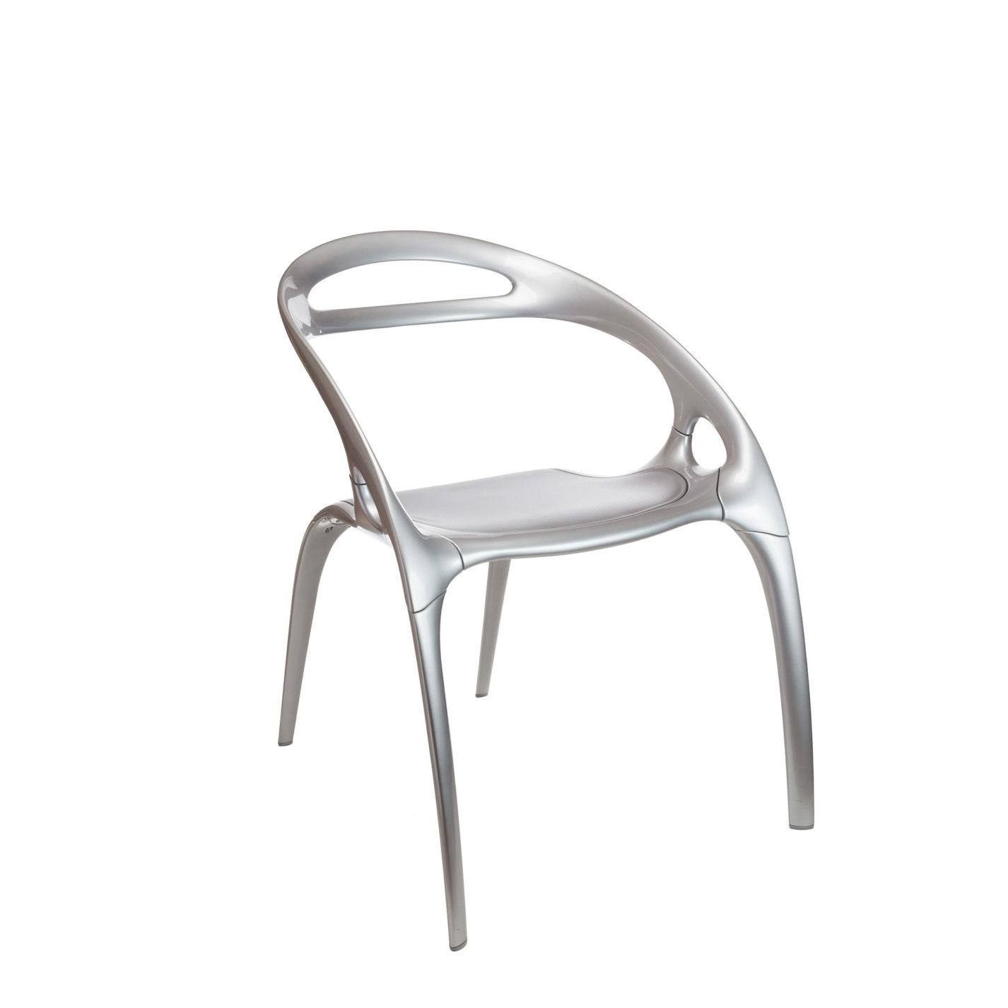 Chaise en métal. Le dossier et les accoudoirs forment un arc continu au-dessus du siège, qui repose sur quatre pieds fins aux courbes harmonieuses.