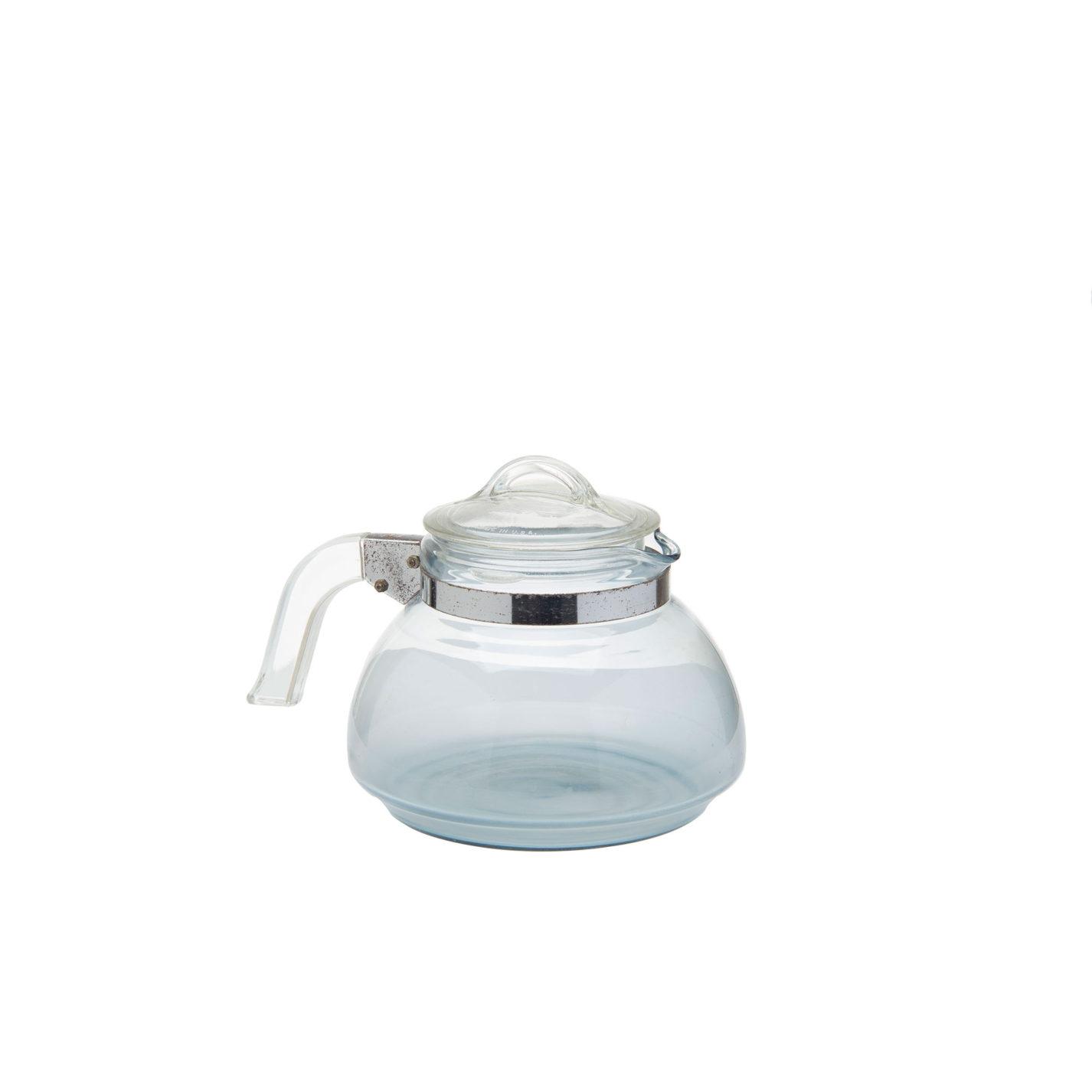 Bouilloire en verre transparent bleuâtre, couvercle en verre et anse en verre fixée par une bande et une ferrure en métal.