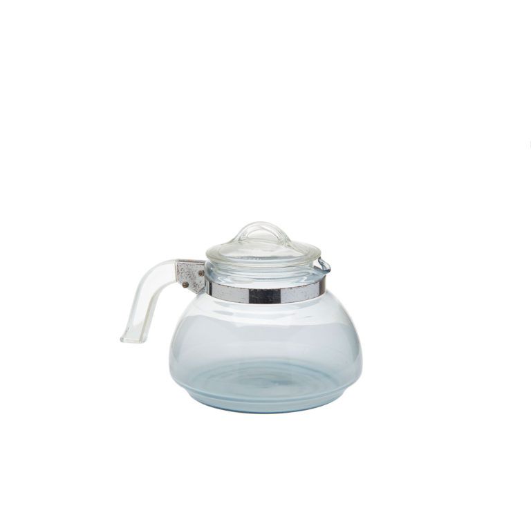 Transparent, bluish glass kettle with a glass lid and with a glass handle connected by a metal band and bracket.
