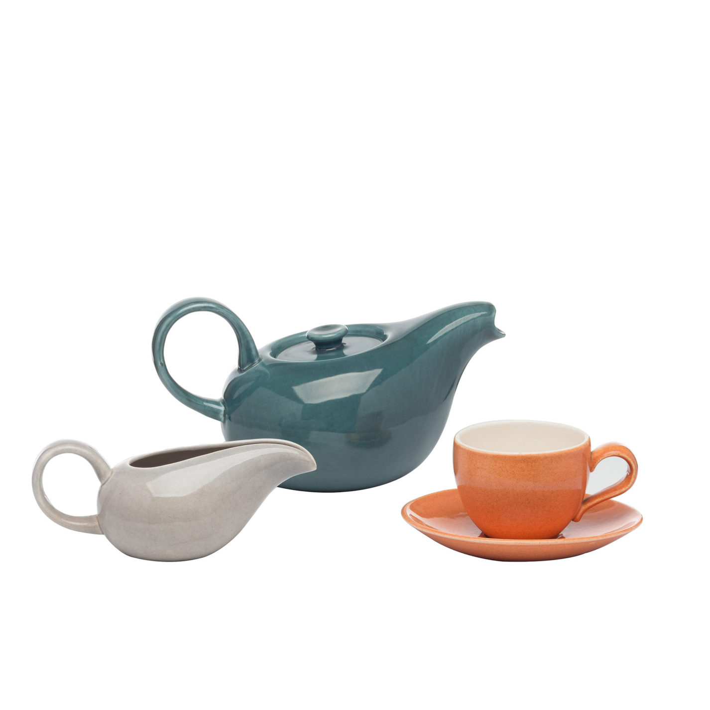 Ceramic dishes. Dark green teapot with elongated spout and rounded handle, elongated grey creamer with open spout and rounded handle, and simple coral-colored teacup with saucer and off-whited cup interior.
