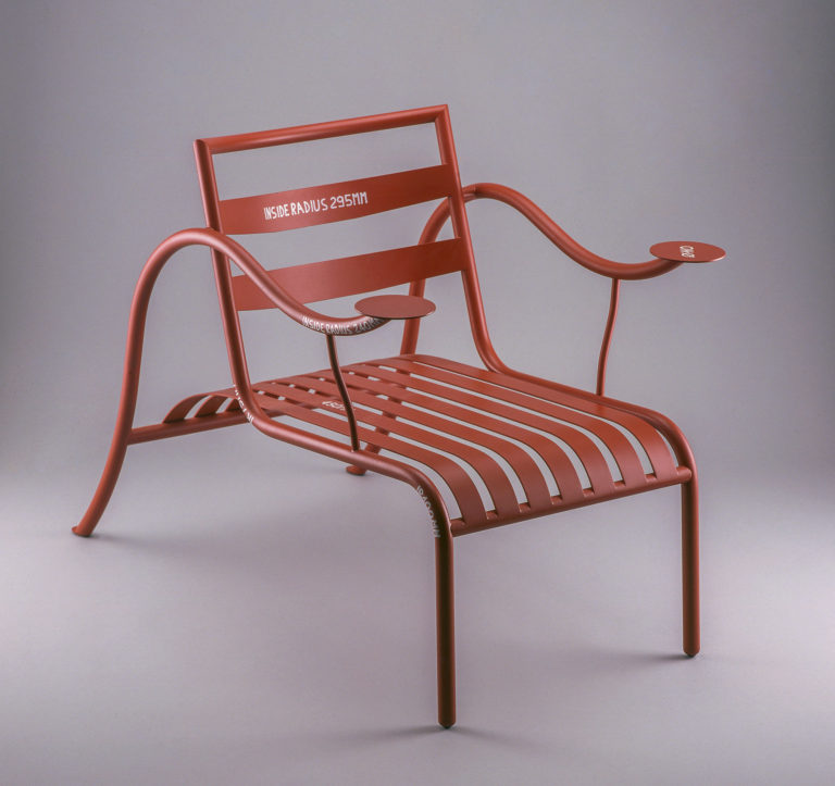 Rust-colored lounge chair in painted steel with curved horizontal back slats. Steel-slat seat extends to curved tubular-steel rear legs, which continue in a single piece to form undulating arms with circular disks at each end.