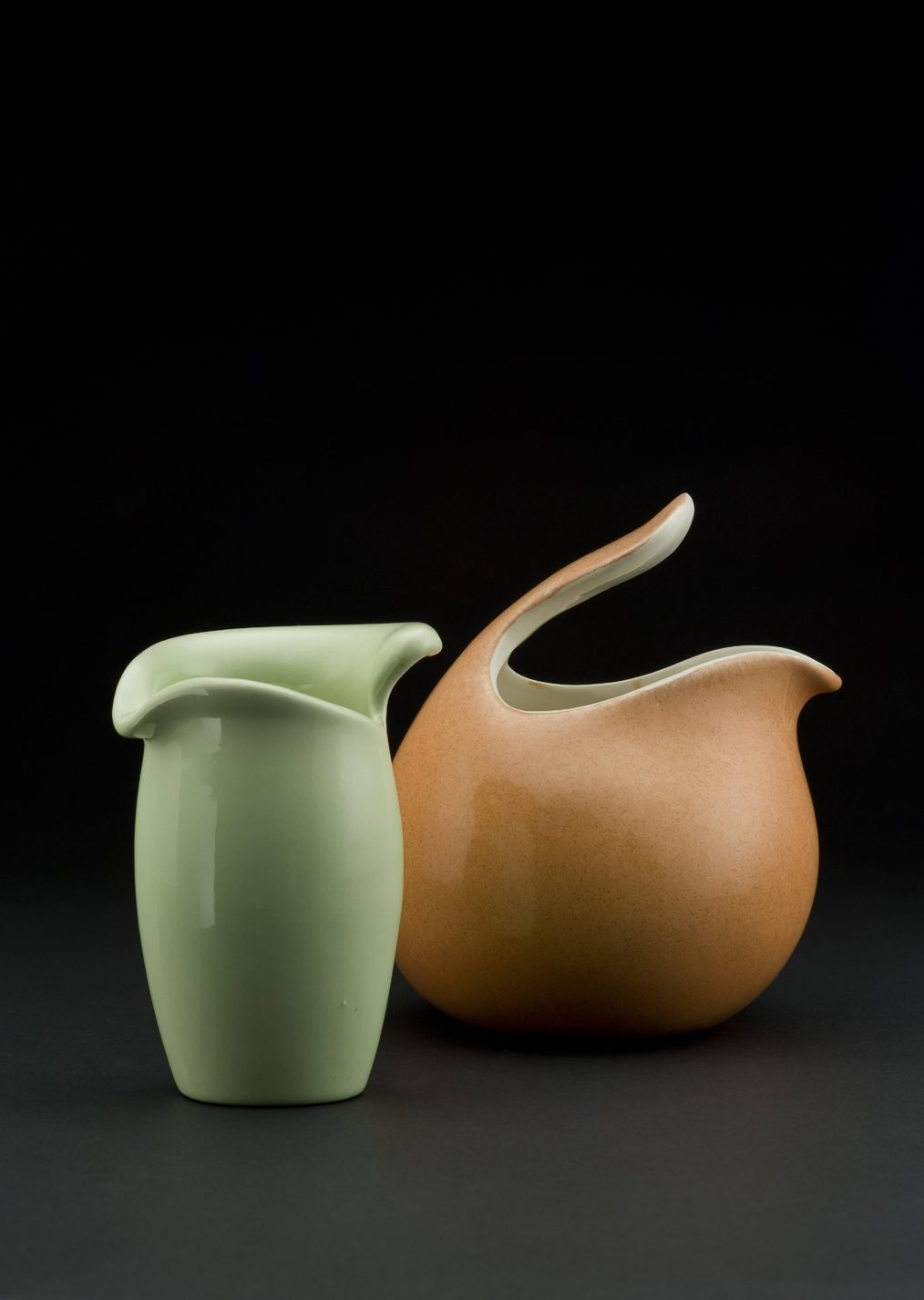 Two ceramic vessels. One pale green, slightly bulbous cylinder with a leaf-like opening at the top, the other terra-cotta colored spherical shape with a handle protruding over the opening at the top.